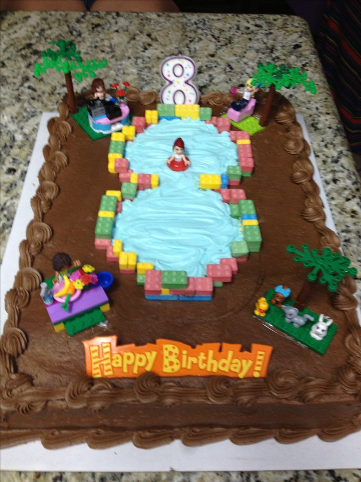 Lego Friends Birthday Cake. I purchased an undecorated Costco cake, used Lego brick candies from the Sweet Factory to form the pool and filled it with blue tinted frosting. I then borrowed my daughters Lego creations to complete the cake.