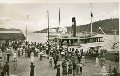 """Akershus fylke Vestby kommune SOON BRYGGE. Mye folk på kaia, rundt båten """"Oscarsborg"""". Brukt.1938 Produsent/foto Oppi"""