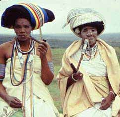 Two Xhosa women in traditional dress. The bead work and clay daubed faces denotes status.
