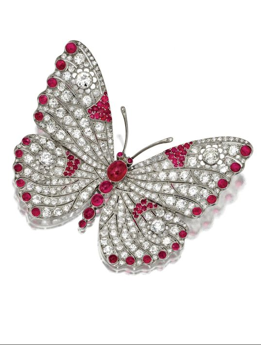 DIAMOND, NATURAL AND SYNTHETIC RUBY BUTTERFLY BROOCH, CIRCA 1930 The insect with openwork wings set with 274 single-cut, old European-cut and round diamonds weighing approximately 18.00 carats, the body, wings and eyes accented with cabochon and round natural and synthetic rubies, mounted in platinum.