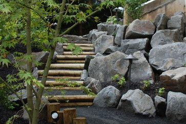 Wood And Stone Steps This is how Ross NW Watergardens conquers steep slopes. Wood steps with boulders and gravel.  Steps and stone retaining...