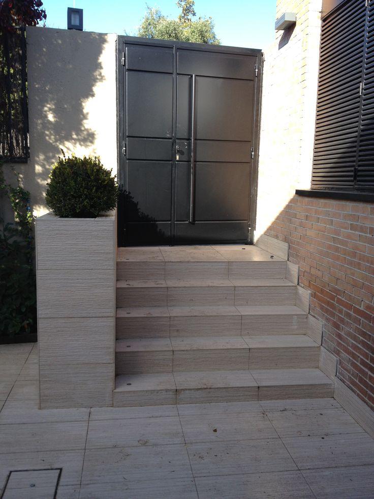 entrada a jardn con puerta de hierro y jardinera