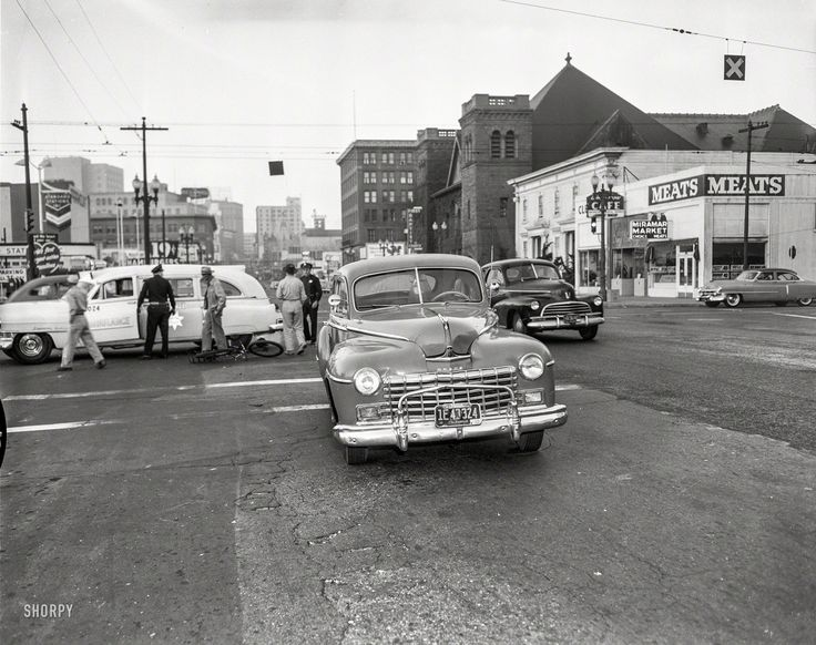 Bicycle vs Dodge sedan downtown Oakland circa 1953. Possibly Telegraph & Grand Ave. At the time, OPD ran the ambulance service.