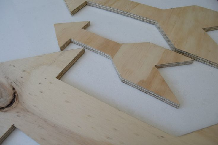 Draw out several arrows in various sizes on your plywood and then use a jigsaw to cut out the arrows. Depending on how neat your cuts are, you may need to lightly sand your arrows