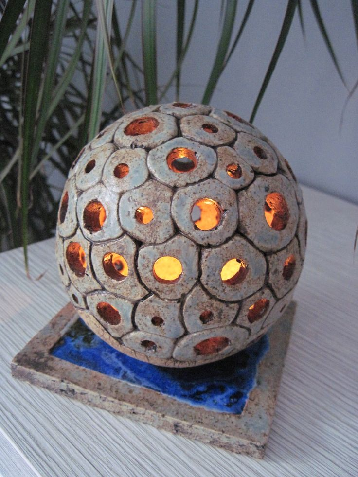 světelná koule Světelná koule o průměru 13 cm, vyrobená ze šamotové hlíny aglazovaná šedomodrou glazurou. Pod koulí je čtvercový kachlík zalitý modrým sklem a také glazovaný šedomodrou glazurou.