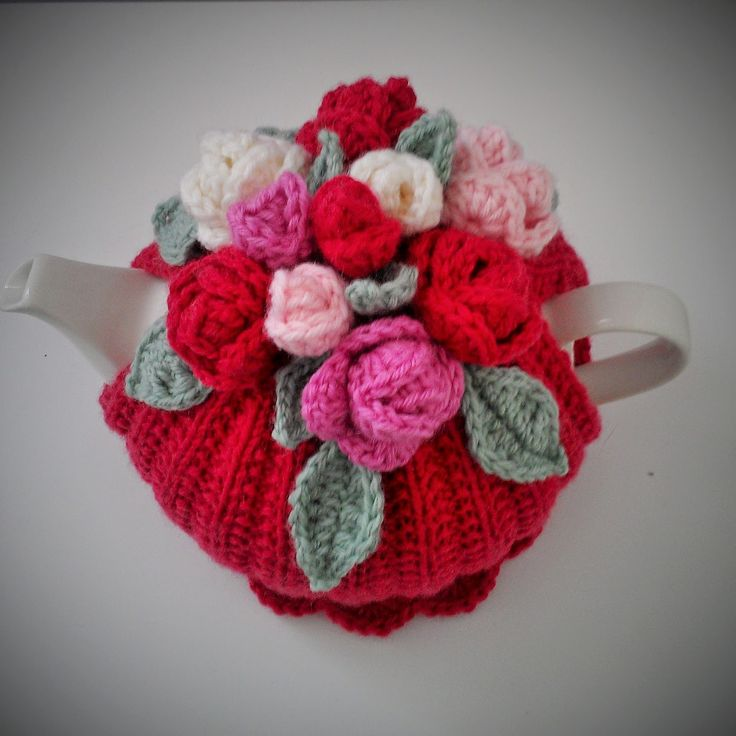 Rose tea cosy         The tea cosy body is fully lined; the outside is knitted using 8 ply wool and 4 mm needles, in moss rib stitch. T...