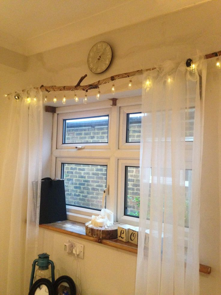 Natural curtain pole with fairy lights.
