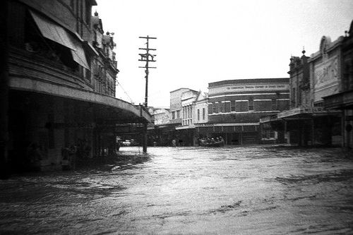 Boat in flooded street during the Maitland Flood, 1955: Lucey Collection
