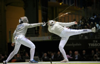 [ID: two sabre fencers in a bout. The one on the left is lunging, but her opponent has parried and is standing with her back leg straight up and out.]  Ibtihaj Muhammad (left) against Leonore Perrus