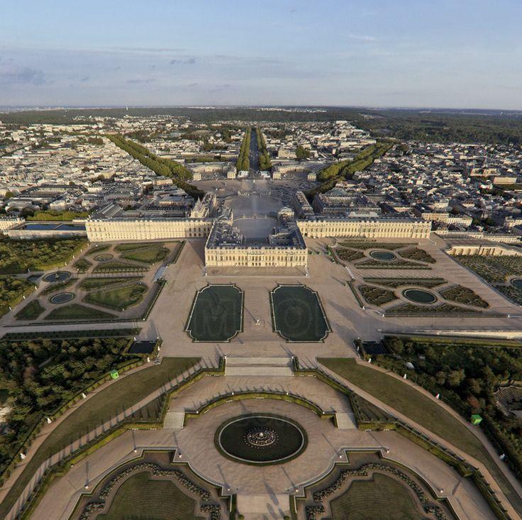 Vue d'ensemble du Château, des jardins et de la ville de Versailles depuis l'ouest. Au premier plan, le bassin de Latone, les Parterres d'eau avec les Parterres d'eau et le Tapis Vert.