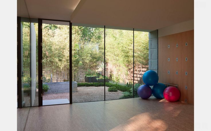 Mid-sized modern home yoga studio with cork floors and beige walls. view from inside to courtyard important
