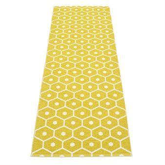 Det stilfulle teppet Honey fra Pappelina er et vevet plastteppe og har et vakkert mønster som minner om innsiden av en bikube. Teppet fins i forskjellige farger og størrelser og kan snus for å gi variasjon. Bruk teppet i gangen eller på kjøkkenet og kombiner den med detaljer i liknende farger for å skape et mer enhetlig inntrykk.