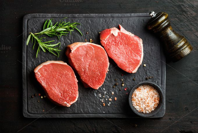 #Raw beef Eye Round steaks  Raw beef Eye Round steaks with spices and rosemary on black slate stone board over dark wooden background top view horizontal composition