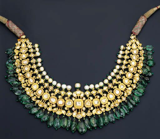 A MODERN DIAMOND, EMERALD AND ENAMEL NECKLACE Designed as a series of flexible diamond-set foliate links suspending an emerald bead fringe to the single-row pearl surmount, the polychrome enamelled reverse decorated in floral motifs, North Indian, contemporary, 35.0cm long