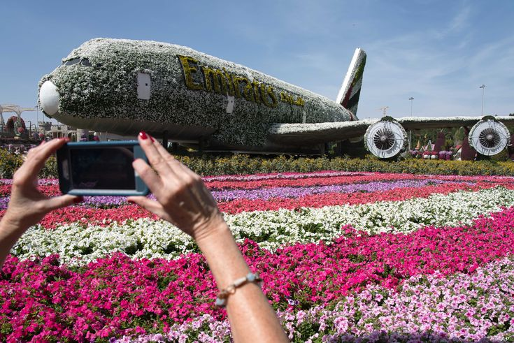 A tourist takes a picture of a mockup of an Emirates