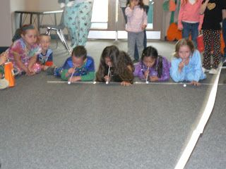 Mrs. T's First Grade Class: Halloween GamesBlowing eyeballs with straws: We raced to see who could blow their candy eyeball from one side to the other the fastest. Toss bean bags in a witch's pot. Wrap each other like a mummy.