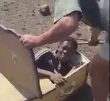 This screengrab from a now-deleted YouTube video depicts the victim, Victor Mlotshwa, being forced into a coffin by one of his tormentors.