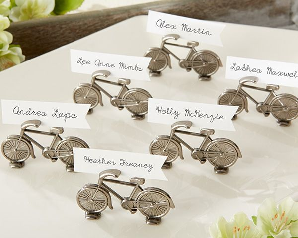 Tandem bicycle place card holders are whimsical wedding décor from Kate Aspen. Each bicycle built for two holds an escort card or a photo of the happy couple.