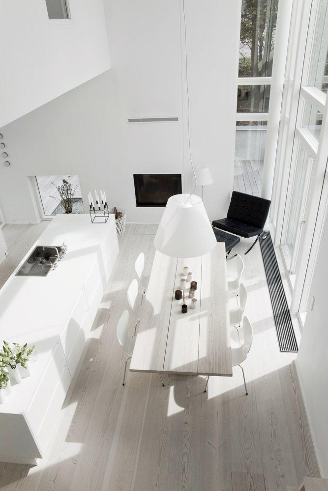 Køkkenet set fra førstesalen er fra TREND køkken/snedkeri og indrettet med arkitekten Mies van der Rohe´s stol fra 1930, der understreger funkis-stilen. Den indbyggede pejs er fra Philip Pejse. Luceplan-lampen er designet af Paolo Rizzatto, de små lygter på spisebordet er fra Oi Soi Oi