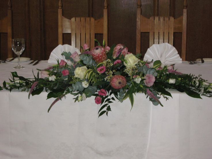 Top table arrangement of Protea, Roses & Lisianthus for a wedding at Hertford College, Oxford. By Sarah Lindsey Flowers