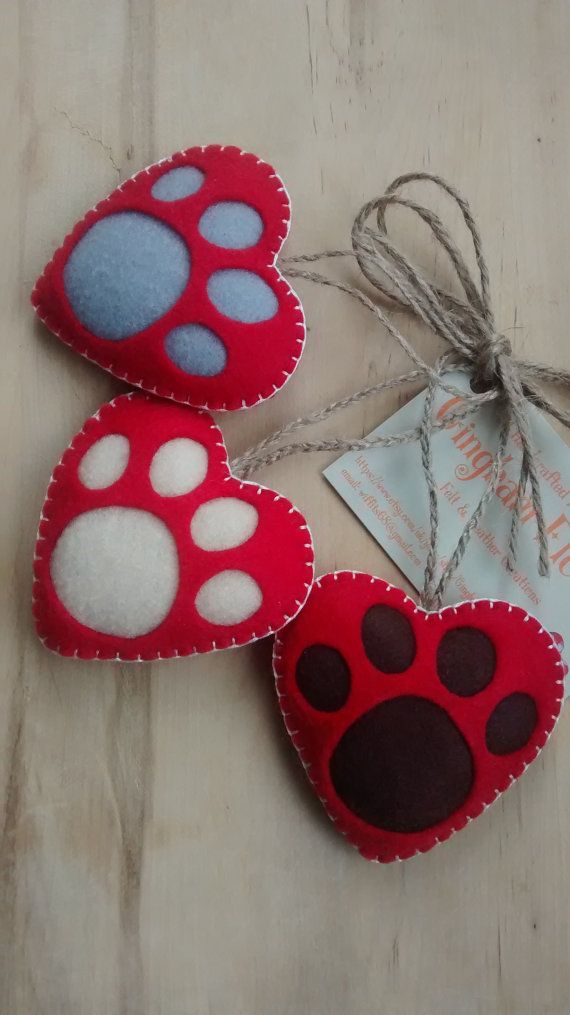 These Heart paw prints would make an ideal tree decoration or to add to your own home decor  Each one is designed and handmade by me in soft felt, filled with polyfill. Each one is attached to a braided hessian twine loop for hanging  Measurements:  Approx 7.5cm wide x 7.5cm high   Overall length of braided loop is approx 8cm long on each decoration.  If you would like a different colour heart, paw print or thread, please leave a note when ordering.  This item is for decoration only and is…