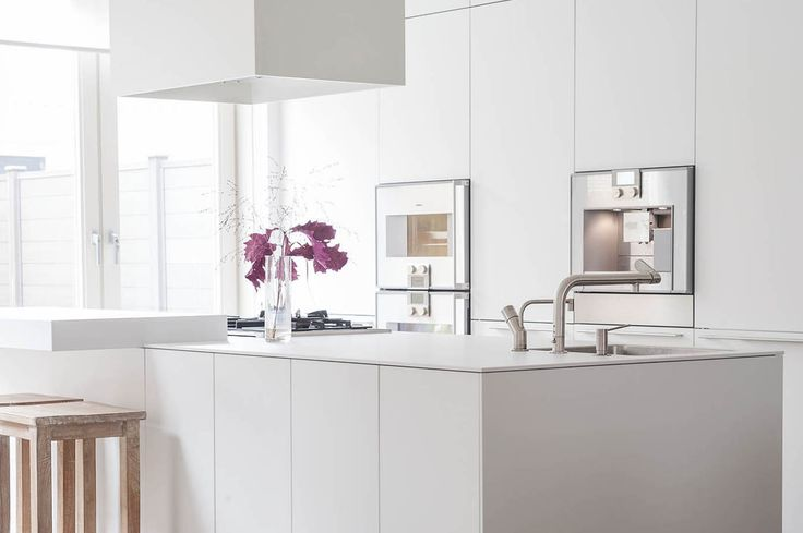 Ontwerp keuken, kookeiland met vaste strak wit uitziende wandkast.