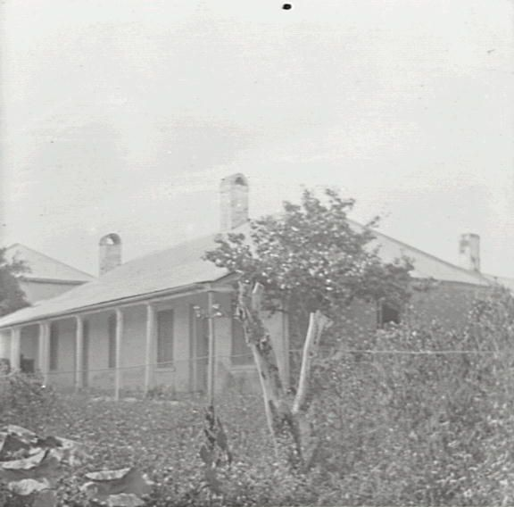 Title: Clarendon House Date & Location: 20 March 1909, Richmond (NSW) Description: Black and white glass lantern slide. Title in ink on upper edge label Notes: Single storey brick home of William Cox, near Richmond; built c. 1804-1806. From negative in Mitchell Library Frank Walker Collection ON 150, Item 627.