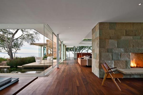Dark floorboards in combination with open spaces, glass, and rough stone walls.