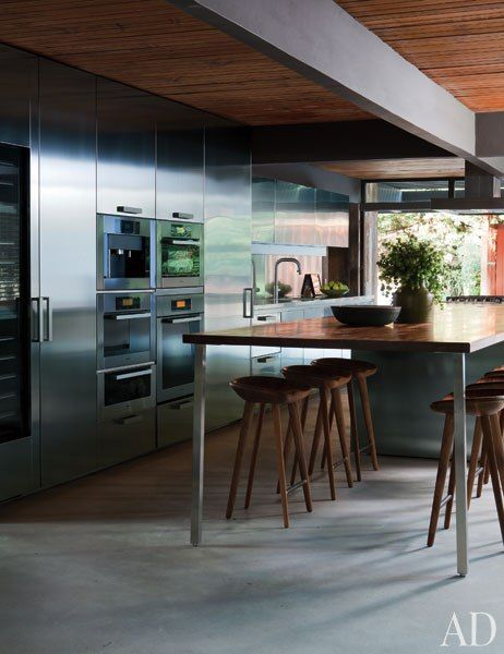 A Los Angeles kitchen is outfitted with a bank of integrated Miele appliances, including a coffeemaker, speed oven, wall oven, and warming drawer. The faucet and cabinets are by Boffi.