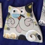 Gatti realizzati in terra bianca con finitura in cristallina opaca. Ogni gatto è modellato a mano senza uso di stampi. Possono essere utilizzati come calamite oppure come decorazione per targhette, cornici e scatoline.