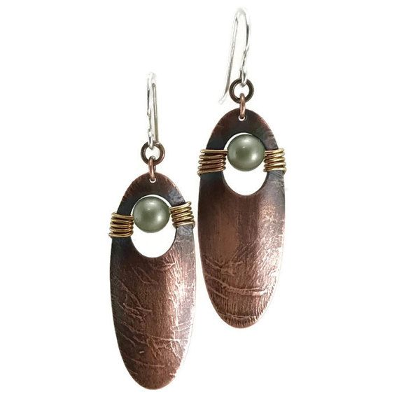 Handmade earrings, artisan mixed metal with boho style. These earrings have a unique texture on a oblong copper disk and brass wire work to hold this green Swarovski pearl. The copper has a rich patina which has been brushed with steel wool for its soft luster effect.These measure 2 inches from tip to tip by 5/8 at the widest portion. They dangle from 20 gauge sterling silver hand forged ear wires. If you prefer copper earrings wires instead of the silver, just send me a message when you...