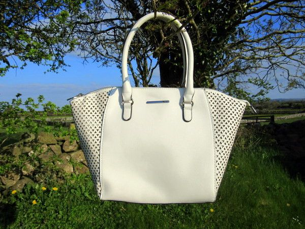 Brilliant White Triangle Perforated Shoulder Bag  Want a classic? Try Primark's brilliant white triangle perforated shoulder bag. It's sleek and timeless with 'winged' trapeze panels. Roomy enough to hold work documents alongside your everyday essentials.