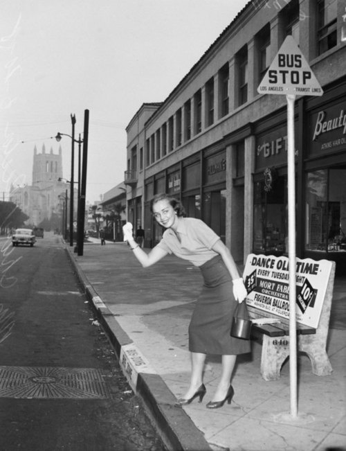 A woman hitchhiking on 6th and Rampart Street during a transit strike in Los Angeles, California, 1955