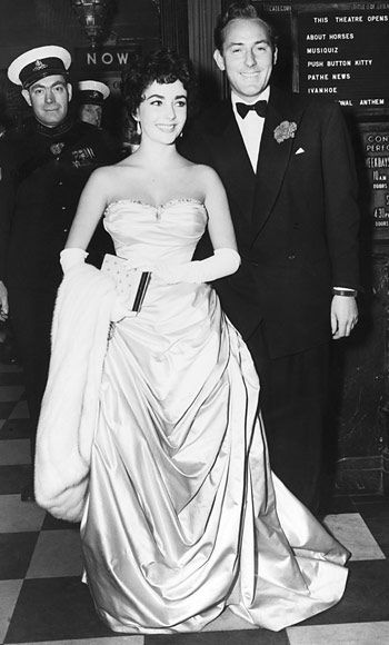 "Elizabeth Taylor and her second husband Michael Wilding. Married 02/21/52, divorced 01/26/57. They had two sons, Michael Howard born 01/16/53 and Christopher Edward born 02/27/55. The ""gentle"" Wilding, 20 years her elder, comforted her after leaving Hilton. After their divorce she admitted that ""I gave him rather a rough time, sort of henpecked him and probably wasn't mature enough for him!"""