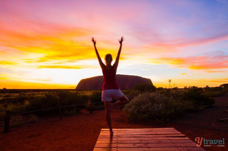Yoga during sunrise at Uluru in Australia