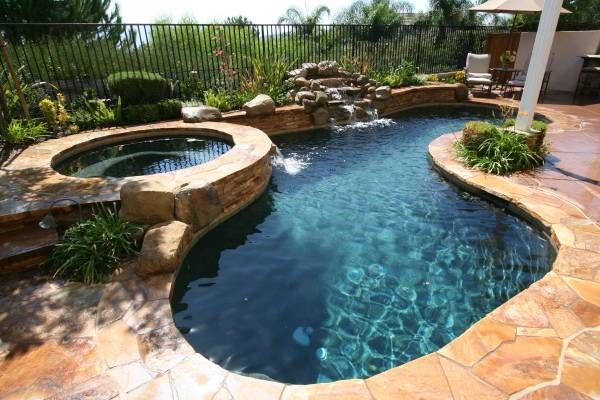 Freeform Pool With Attached Spa Spilling Into The Pool And Rock Waterfall Natural And Freeform