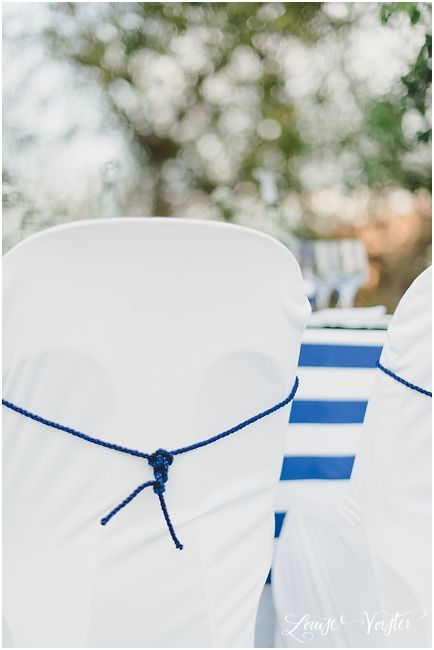 Close up of white chair covers and blue rope chair tie.