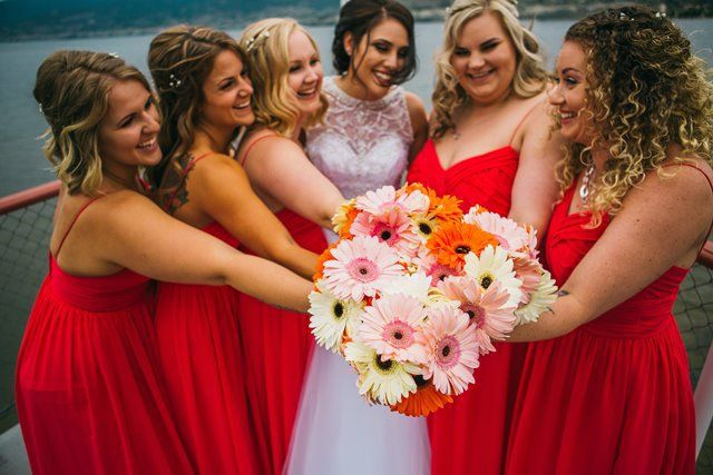 Bride and Bridesmaids with flowers on the bow - Photo by Justine Russo