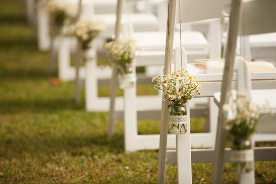 for ceremony: glass jar or tin can or mini buckets + baby's breath (or other tiny flowers); tie/chain/hang to chairs.
