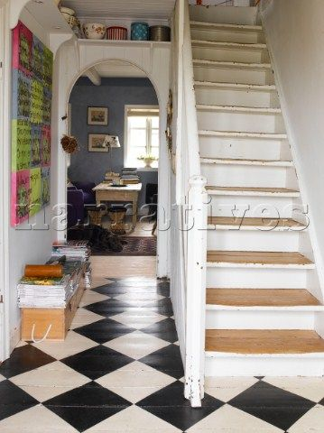 White hall and staircase with painted checkered floorboards. Love this look, with neutral decor but still packing a punch
