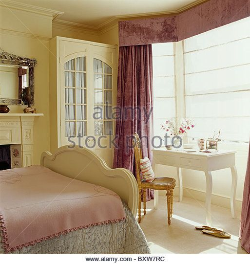 Purple heavy silk curtains and cream blind on bay window in townhouse bedroom with fitted wardrobe