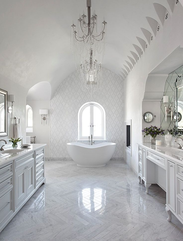 Artistic Tile I Designer Heather Scott I This pristine masterbath uses texture and pattern to add sophistication to a neutral white palette. Our custom Bianco Carrara Herringbone #marble floor creates the foundation, while the shell ribbons of our Claridges mosaic climb through a background of pristine Thassos marble on the wall surrounding the window.
