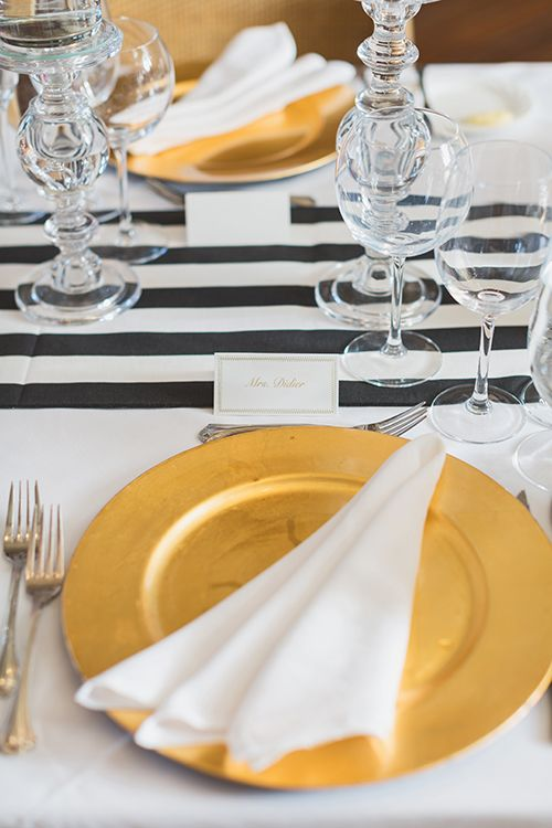 Gold charger pop against black-and-white striped table runners   @nickivitalic   Brides.com