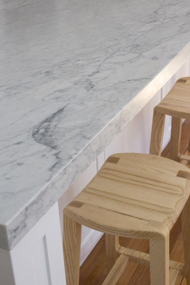 Carrara marble benchtop edge detail with timber bar stools below