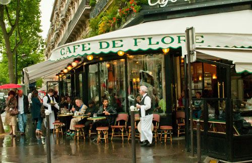 """A spring rain dampens the streets, but not the spirit of Paris nor the ambiance of its quaint cafes. One of the more famous, Café de Flore, has changed little since World War II."" —jerrycaz"