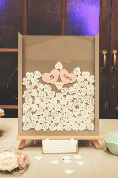 Guests sign their name on a little wooden heart and drop it in a shadow box frame. Way better than a guest book