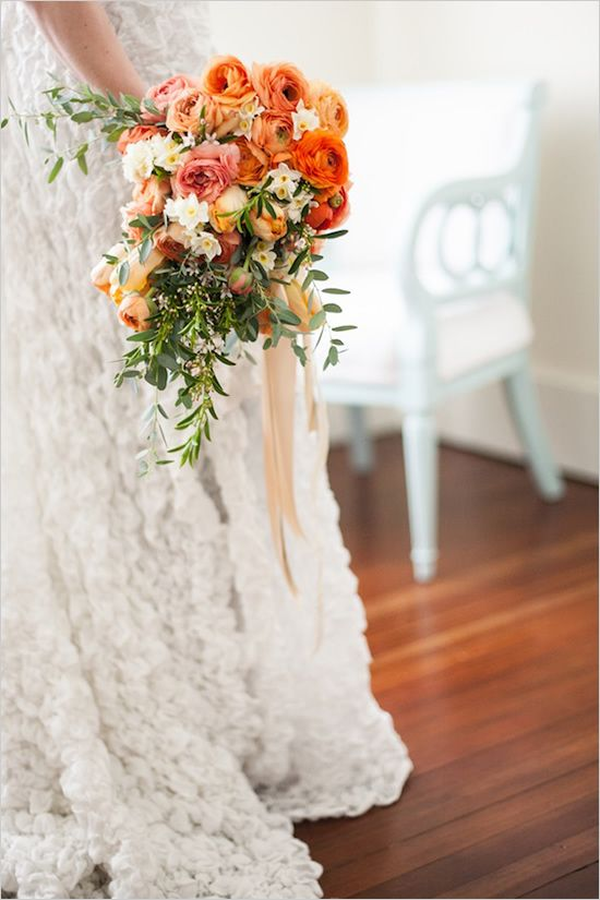 hand tied cascade bouquet is tied with gold, blush and lace ribbons. Stems of ranunculus in shades of orange, peach, coral and pink, orange and green parrot tulips, narcissus (which not only look pretty but also smell amazing), and sprigs of citrus blossom and eucalyptus were used to make this pretty bouquet. The cascade style and fluffy ranunculus make the bouquet pretty and feminine.  <3 the cascading ribbons and greens  Designed by Finch & Thistle Event
