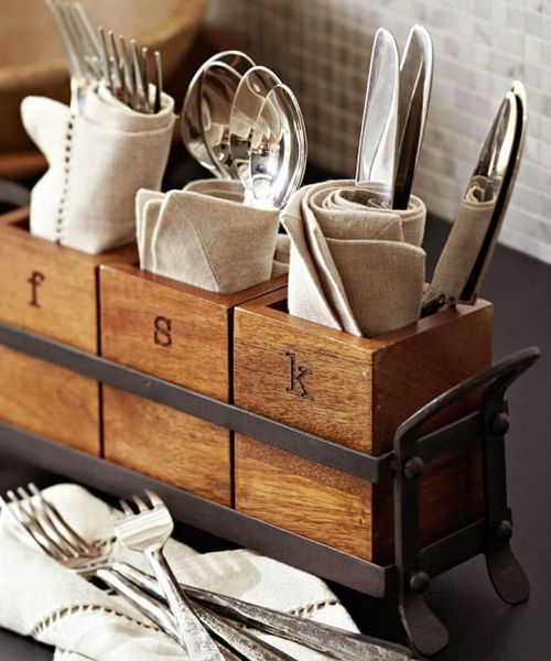 Vintage Flatware Caddy Vintage Flatware Caddy: Vintage Blacksmith flatware Caddy. Three mango wood coffers are set inside a blackened iron frame to create this handsome caddy, perfect for sharing serving utensils, napkins and flatware. Curved handles make it easy to pass around the table.