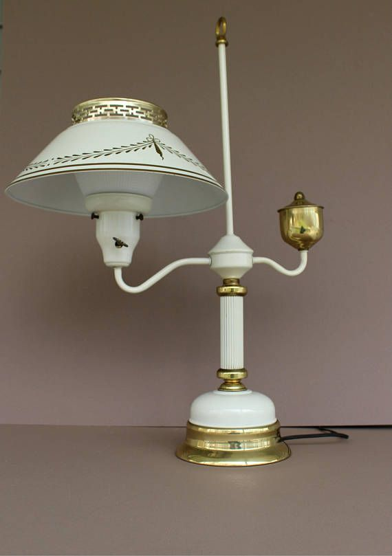 Early American style, off white metal toleware, tall accent table lamp. Decorative arts vintage 1960s, 1970s tole-ware lamp is painted an off white, neutral cream with a gold luster accent trim and detailing. Metal lamp shade has hand stenciled gold trim and detailing wrapping around the metal shade. Shade has an openwork rim on top of shade for even more appeal. Metal tole-ware shade rests on a thick white textured milk glass Corning globe shade so there is no exposed naked bulb or harsh…