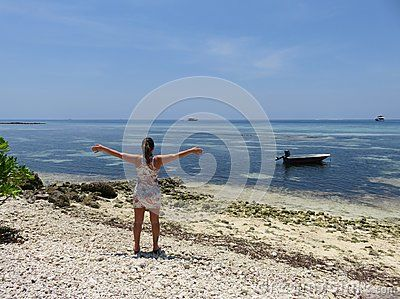 View of Maldives Sea, from Maafushi Islands, with girl and a small boat on the water.